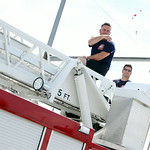 Members of the Lorain Fire Department throw candy to spectators lining Broadway as they ride in the bucket of the department's fire truck. ANNA NORRIS/CHRONICLE