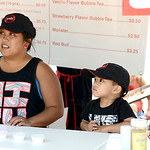 Dannelie Cacas and Rayden, 3, of Strongsville, serve sushi from Bento Express Yoh: Sushi at the Japanese booth at the Lorain International Festival on Saturday. KRISTIN BAUER | CHRONICLE
