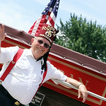 A member of the Al Koran Shriners waves to a crowd as he rides on an antique fire truck in the parade. ANNA NORRIS/CHRONICLE