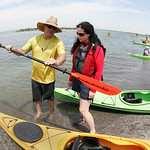 "Tim Truman of Current Designs Kayaks and Wenonah Canoe explains to prospective kayak buyer Deirdre Garvey of Cleveland how to ""feather"" a kayak paddle so that the blade comes out of the wate …"