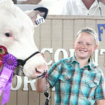 Madison Lewis, of Oberlin, smiles as she holds her Grand Champion Dairy Steer during the 2014 Lorain County Junior Fair Livestock Sale Saturday morning. Lewis' dairy steer was purchased by B …