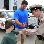 Abe Mastellone, left, and father Brian, of Amherst,  are 'handcuffed' by Barney Fife, played by Todd Beckett of Massillon, for their giving a charitable donation to the Boys and Girls Clubs  …