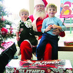 Grayson, 1, and Brock, 3, visit with Santa after donating toys.