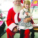 Cameryn, of Elyria, sits with Santa after donating to the Not Forgotten Box for the first time.