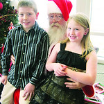 Carsen, 10, and Braeden Ponozocha, 7, of Elyria sit with Santa after donating to the Not Forgotten Box.