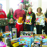 The Lorain County Auditor's Office raised $800 to purchase toys by allowing employees to have dress-down days in December. Picture are Paul Nishinain, left, Jennifer Kelleher, Craig Snodgras …