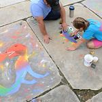 Aubrynn Reichle, 7, and her father, James, of Oberlin, work on her dinosaur design during Oberlin's annual Chalk Walk. KRISTIN BAUER | CHRONICLE