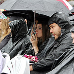 Oberlin College graduates attempt shield themselves from the rain under umbrellas and ponchos while listening to commencement speaker Tracy Chevalier, a 1984 graduate and novelist, during th …