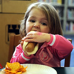 Payton Hazelett, 2, of Elyria, has a hot dog at Opening Day event at Elyria Central Branch Library Mar. 31.  Steve Manheim