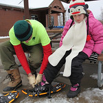 Madeline Fairweather (age 9) gets fitted for snow shoes by her father Tim Fairweather at Sandy Ridge Reservation – Johnson Wetland Center in North Ridgeville. photo by Ray Riedel