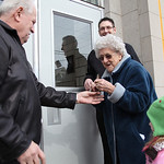 Elsie McKinnon hands the scissors to Wendell Strunk (left) after she cuts  the ribbon over the doors at the restored school. Principal Joe Akosi looks on from Elsie's right. Elsie McKinnon g …