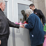 Wendell Strunk (left) helps guide Elsie McKinnon's hand as she cuts  the ribbon over the doors at the restored school. Principal Joe Akosi (background) helps hold the ribbon steady. Elsie Mc …