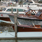 Vintage boats moored from close to far are a Chris Craft 17-foot; 25-foot Lyman; 26-foot Lyman; 17-foot Chris Craft ski boat; a Higgins (white hulled boat with windshield propped open) and a …
