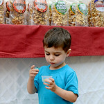 Coleton Phillips, 2, of Wellington, tries popcorn at the American Classic Snack Company booth at the annual Wellington Cheese Heritage Festival in downtown Wellington on Friday.  KRISTIN BAU …