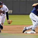 Cleveland Indians' Mark Grudzielanek, right, is safe at third as Minnesota Twins third baseman Brendan Harris fields a ground ball by Indians' Mike Redmond in the fifth inning of a baseball …