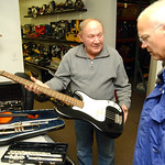 Steve Smith, left, owner of Pawn-N-Park at 2041 N. Ridge Rd, holds a bass guitar with other donated instruments for Mark Wainwright, lead instrumental music teacher for Elyria City Schools o …