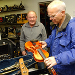 Mark Wainwright, right, lead instrumental music teacher for Elyria City Schools, looks over musical instruments donated by Steve Smith, owner of Pawn-N-Park at 2042 N. Ridge Rd. Dec. 2.   St …