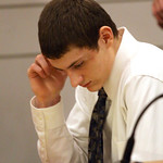 Daniel Kovarbasich sits alone at the defense table with his head down during a break in the trial.