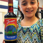Emilia Sansotta, 8, a third-grader at Redwood Elementary in Avon Lake, holds a bottle of Torani Raspberry syrup with her winning label artwork.  Steve Manheim