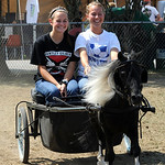 Melanie Gott, left, and Megan Pitts, both of Wellington, take a ride with Satin Doll, a miniature horse, at Lorain County Fair on Aug. 23.   Steve Manheim