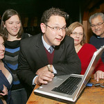 Dan Ramos looks at early election results at his election night gathering point at Mutt & Jeff's.  Left to right are Erin Synk, campaign manager; Diane Ramos, sister; Dan Ramos; and mother a …