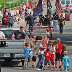 Children and adults swarm one of the trucks giving out American Flags elyria Parade. Elyria Parade. Photo by Tom Mahl