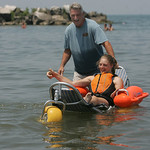 29JUN12 Samantha Taylor enjoys the special beach equipment –the Mobi Chair–a type of amphibious beach wheelchair–that's available at Lakeview Park. Her dad Aaron is behind her. P …