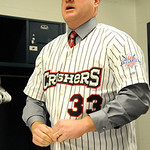 Jeff Isom puts on his jersey after being named the new Crushers manager at All Pro Freight Stadium on Dec. 19. Steve Manheim