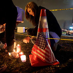 Janai Roberts, 17, lights a candle in front of a growing display of flowers, candles, and messages of sympathy in front of the Forza Coffee Company in Parkland, Wash., Monday, Nov. 30, 2009, …