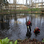 Shaun Darby, left, and Curtis Filleau, both members of the Pierce Co. Sheriff's dive team, search a pond at the Willows Apartments, Monday, Nov. 30, 2009, in Parkland, Wash. near the scene w …