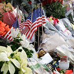 Flags, flowers, and other items are shown Monday, Nov. 30, 2009, at a memorial at the Lakewood Police headquarters in Lakewood, Wash. Four Lakewood Police officers were fatally shot Sunday m …