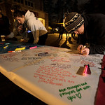 PLU student Jon Wedell writes a message on a paper-covered table at a vigil held in memory of four slain Lakewood Police officers, Monday, Nov. 30, 2009, at Pacific Lutheran University in Pa …