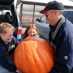 Brendan Roof, 9, sister Lauren, 7, and their father Doug, of Westlake, move a jumbo-sized halloween pumpkin into their car at Fitch's Farm Market in Avon on Oct. 13. There are wagon rides …