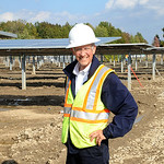 Rob Lamppa, project liason, and Director of Sustainable and Energy Management at Oberlin College, stands between a bank of solar panels in the solar array project in New Russia Twp. on Oct.  …