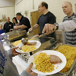 St Mary's held an Easter Dinner after Masses at the Newton Commons on St. Mary Way. Lee Sebesta, right, ladles corn onto the plates of servers who will take the meals to those waiting at tab …