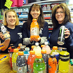 Chessey Verhovec, left, Phyllis Kuntz, and owner Michelle Henke of Piggy's Main Street Market in S. Amherst hold gatorade, powerade and other drinks for the Tough Mudder event this weekend a …