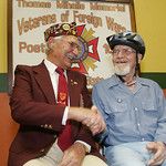 Former POWs Edward Yursky, left, and Paul Kleefeld shake hands on the stage at the Elyria VFW Thomas Mihalis Post 1079.  Yursky was a tail gunner on a B-17 and Kleefeld was in the 87th infan …