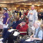 Steve Fogarty— Members of the audience stand during the playing of the National Anthem at the Wesleyan Village Veterans ceremony.