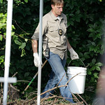 An investigator carries out a bucket  Sunday, July 21, 2013 near where three bodies were found in East Cleveland, Ohio. Searchers rummaging through vacant houses in a neighborhood where thre …