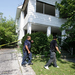 East Cleveland police search a house Sunday, July 21, 2013, where a body was recently found  in East Cleveland, Ohio. The bodies, believed to be female, were found about 100 to 200 yards (90 …