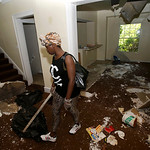 Sanautica Hicks-Ross, 18, searches an abandoned home Sunday, July 21, 2013, near where three bodies were found in East Cleveland, Ohio. Hicks-Ross is an East Cleveland resident. Police Chief …