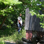 An East Cleveland police officer searches the backyard of a house Sunday, July 21, 2013, where one of three bodies were recently found, in East Cleveland, Ohio. The bodies, believed to be fe …