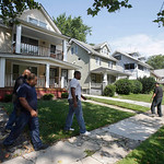 East Cleveland police officers search a neighborhood Sunday, July 21, 2013, near where three bodies were recently found, in East Cleveland, Ohio. The bodies, believed to be female, were foun …