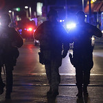 Officers wearing tactical gear arrive at the Watertown neighborhood of Boston, Friday, April 19, 2013. Reports of explosives being detonated and police are telling reporters to turn off thei …