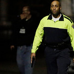 Police officers with their weapons out search for a suspect Friday, April 19, 2013, in Watertown, Mass. A tense night of police activity that left a university officer dead on campus just da …