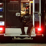A police officers rides in the back of a van with his weapons out Friday, April 19, 2013, in Watertown, Mass. A tense night of police activity that left a university officer dead on campus j …