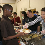 Brandon Swain (foreground) and Jeremy Saxon (left) serve Thanksgiving meals at St. Mary's. Karen Davis is filling Brandon's serving plate. Alongside Karen Davis are Mr. Scarvelli and his dau …