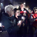 Beverly Phelps shields her candle from the wind and silently mourns the victims of the Connecticut shooting spree. photo by Ray Riedel