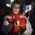 Peg King shields her candle from the wind and silently mourns the victims of the Connecticut shooting spree. photo by Ray Riedel