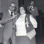 Leonard Kopowski, regional vice president for Tupperware, honors Eva Mae Pugh at a regional sales meeting. At the podium in the background is Gaylin Olson, a former Tupperware president.